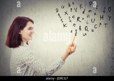 Jeune femme d'affaires, tenant un crayon dans sa main, le dessin des lettres de l'alphabet. L'éducation et communication concept isolé sur fond de mur gris.