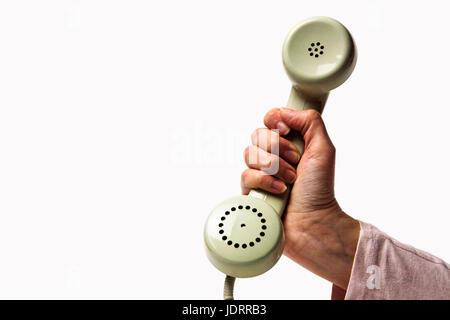 Main tenant un vert clair retro phone isolé sur fond blanc