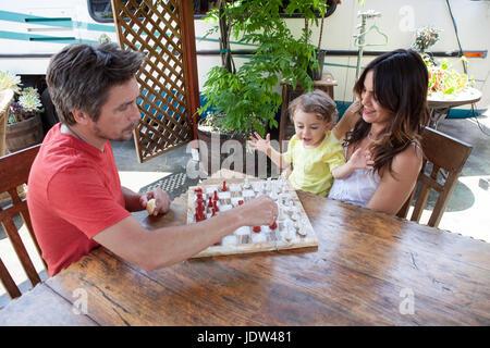 Les parents et le fils jouant aux échecs