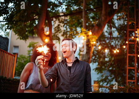 Young man holding sparkler at garden party