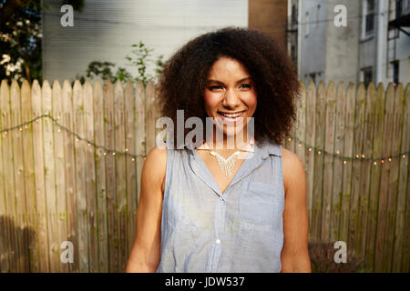 Young woman standing in front of garden fence, smiling Banque D'Images