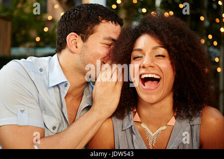 Jeune homme chuchoter à laughing woman at garden party Banque D'Images