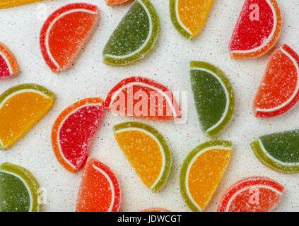 Aliments colorés de l'arrière-plan sous forme de tranches marmelade d'agrumes répartis au hasard sur une table gris. Banque D'Images