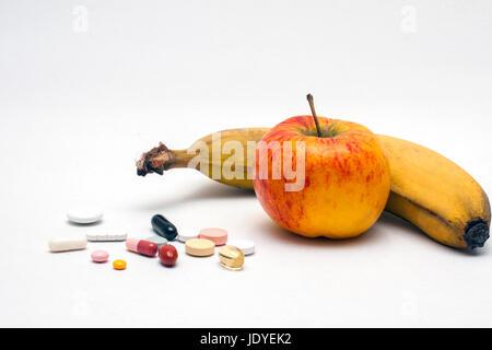 Verschiedene bunte Tabletten, Apfel und Banane, isoliert
