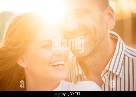 Couple heureux ont beaucoup de temps ensemble - photographié au coucher du soleil contre le soleil Banque D'Images