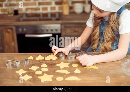 Vue de côté de petite fille en faisant des cookies en forme de chapeau de chef de cuisine Banque D'Images