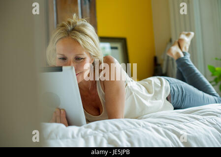 Young woman lying on bed watching digital tablet