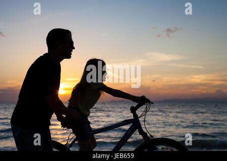 Père et fille jouer sur la plage, à l'heure du coucher du soleil. Concept de famille accueillante. Banque D'Images