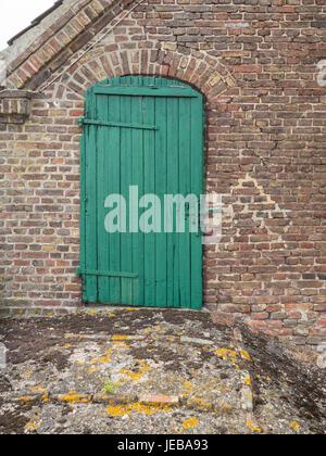 Vieille porte en bois vert sur une grange en brique en Allemagne Banque D'Images