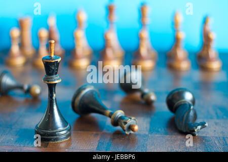 Pièces des échecs en bois ancienne sur un ancien échiquier. Sur un fond bleu.