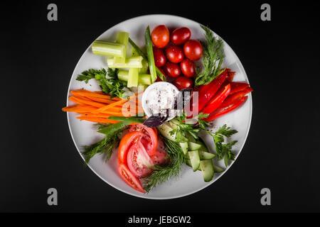 Assortiment de légumes sur une assiette. Sur un fond sombre, vue d'en haut. Banque D'Images