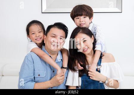La famille Chinoise Asiatique assis sur le canapé dans le salon à la maison. Banque D'Images
