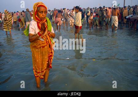 L'Inde, le Bengale occidental, Sagar, Sagar pèlerins Festival femme âgée porter du rouge et jaune sari priant dans Banque D'Images