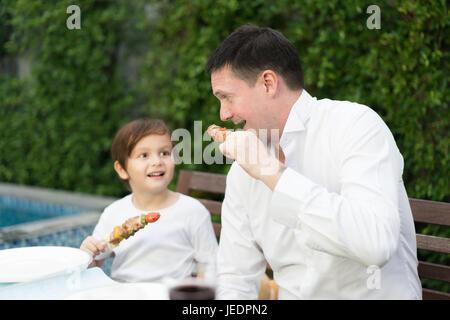 Père avec peu bcute boy eating barbecue en famille l'heure du déjeuner à la maison. Banque D'Images