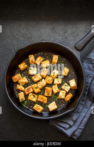 Tofu frit aux graines de sésame et d'épices sur le poêle en fonte, copiez l'espace. Sain ingrédient pour la cuisson Banque D'Images