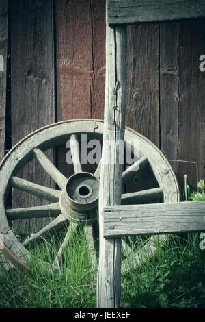 Vieille roue de chariot à l'extérieur du mur du bâtiment rural. Nostalgie rustique en bois objet. Banque D'Images