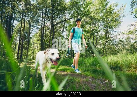 Jeune homme marchant avec son chien (labrador retriever) en forêt. L'heure d'été et les vacances thème. Banque D'Images