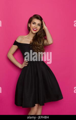 Belle jeune femme élégante en robe de cocktail noire tient la main dans les cheveux, en souriant et en regardant Banque D'Images