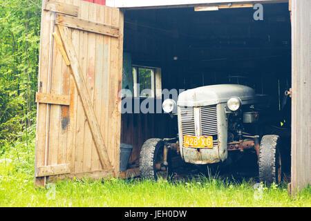 Vieux tracteur gris dans une vieille grange rustique avec un fond vert Banque D'Images
