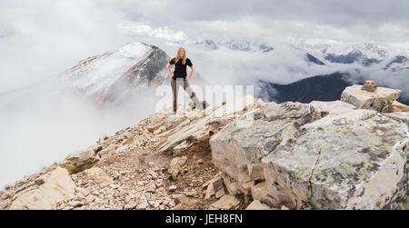 Un female hiker pose seul pour un portrait d'aventure au sommet d'une montagne sur les sentiers de randonnée de Banque D'Images