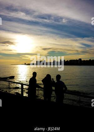 Les adolescents en regardant le coucher du soleil Banque D'Images
