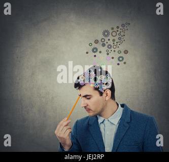 La pensée et la création d'affaires réussi avec un crayon a fait à sa tête une coloruful cerveau fait du pignon Banque D'Images