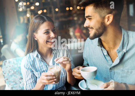 Young attractive cheerful couple on date in coffee shop Banque D'Images