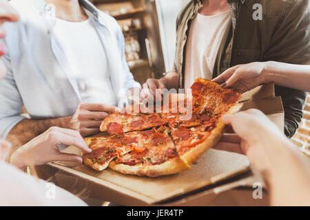 Les jeunes gens à faire la fête, manger une pizza à la maison partie Banque D'Images