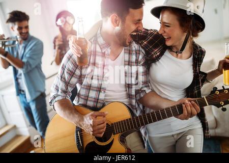 Cheerful young friends having party ensemble et jouant des instruments Banque D'Images
