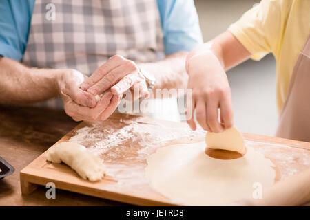Petit-fils et son grand-père et la cuisson de la pâte pour faire des biscuits avec des ustensiles de cuisine à la Banque D'Images