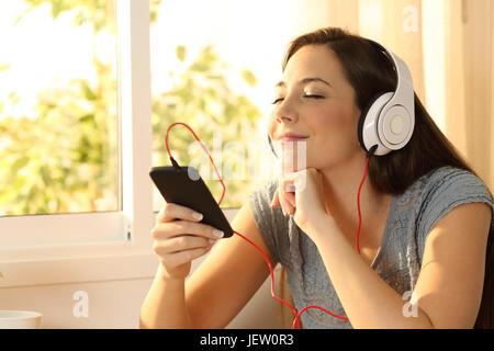 Relaxed woman listening music avec un casque et un téléphone intelligent à la maison avec une fenêtre à l'arrière-plan