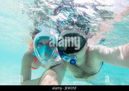 Un couple dans l'amour en tenant sous l'océan Indien en selfies, aux Maldives. Eau turquoise. Banque D'Images