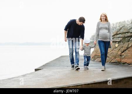 Famille avec le fils marche sur jetty Banque D'Images