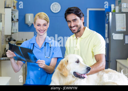 Femme vétérinaire et propriétaire de chiens de sourire et de poser Banque D'Images