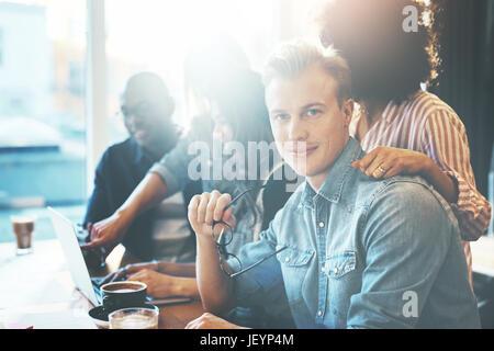 Handsome man holding eyeglasses assis à table de conférence avec des collègues. Fenêtres lumineuses en arrière-plan. Banque D'Images