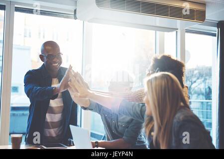 Avec un groupe d'entrepreneur célébrant les partenaires d'affaires en bureau avec fenêtres lumineuses en arrière Banque D'Images