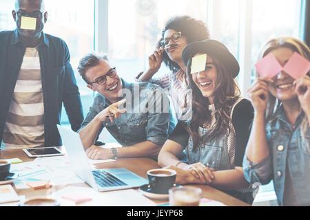 Groupe de plaisanter jeunes adultes divers collègues jouant avec les notes sur leurs visages comme une distraction au cours d'une réunion