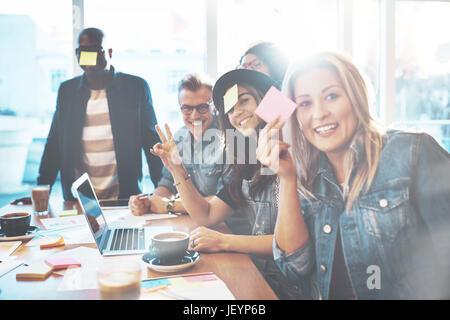 Équipe diversifiée d'employés de bureaux, hommes et femmes jouant avec les notes au tableau