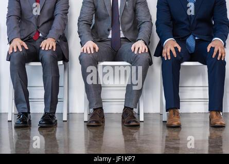 Les hommes d'affaires en costumes assis sur des chaises blanches en salle d'attente, réunion d'affaires. Banque D'Images