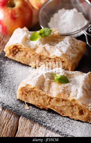 Strudel aux pommes saupoudré de sucre en poudre sur la table. La verticale