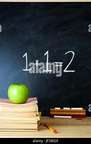 Un tableau de l'école de l'enseignant et bureau avec pile de livres d'exercices et une pomme. La somme '1 + 1 = Banque D'Images
