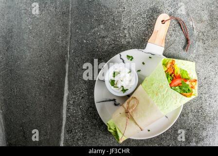Cuisine mexicaine. L'alimentation saine. Vert: sandwich roulé aux épinards tortillas lavash, poulet frit, légumes Banque D'Images
