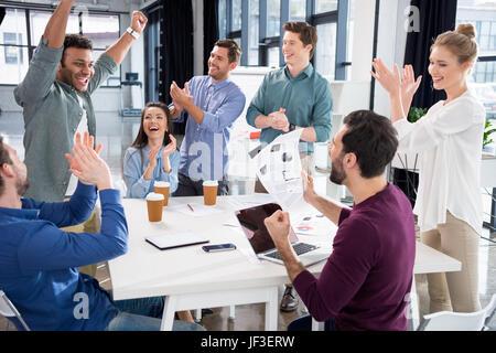 L'équipe d'affaires des succès à célébrer ensemble sur vert au travail, Jeune professionnel concept de groupe Banque D'Images