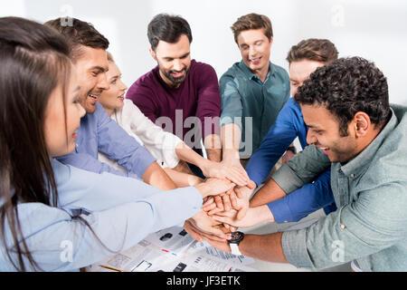 L'équipe d'affaires ensemble sur highfive donnant au travail, Jeune professionnel concept de groupe Banque D'Images