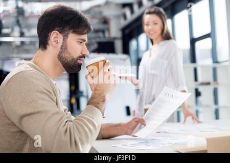 Smiling young businesswoman looking at businessman de boire du café et à la recherche à contrat Banque D'Images