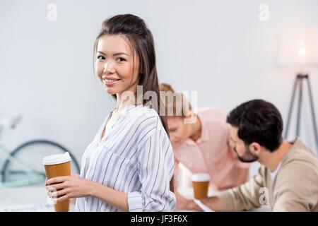 Portrait of smiling businesswoman holding Coffee cup avec des collègues près de par Banque D'Images