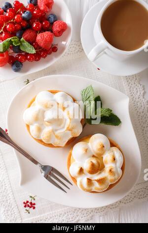 Tartelettes au citron meringuée, avec de petits fruits et de café sur la table. close-up vertical Vue de dessus. Banque D'Images