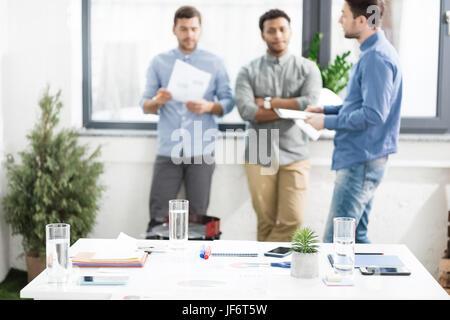 Vue rapprochée des documents et cartes d'affaires sur 24 et les hommes d'affaires, debout derrière le concept d'équipe Banque D'Images