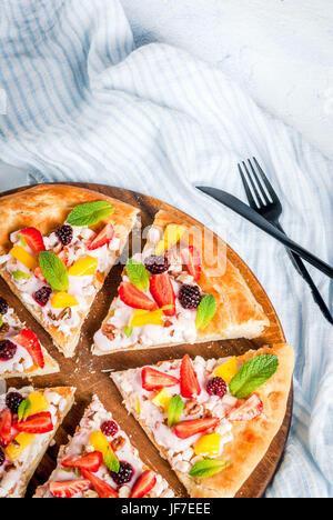 Des collations d'été. La nourriture pour partie. Pizza aux fruits avec de la crème, de cassis, de yaourts, de fraises, mangues, pêches, bananes, mûres, de chocolat, de noix, de la menthe Banque D'Images