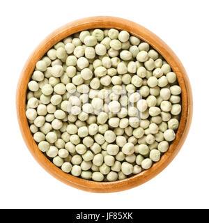 Pois verts séchés dans un bol en bois. Les petites graines sphériques vert clair à partir des cosses de Pisum sativum, Banque D'Images